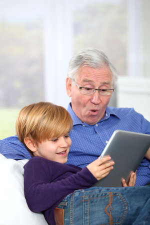 grandchild: Grandpa with little boy using electronic tablet
