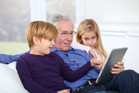 Grandfather with kids using electronic tab photo