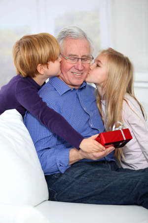 joy of giving: Kids giving birthday gift to their grandfather Stock Photo