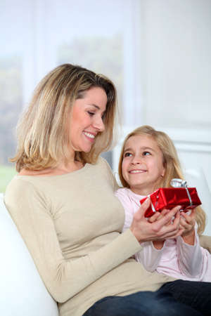 Little girl offering present to her mom photo