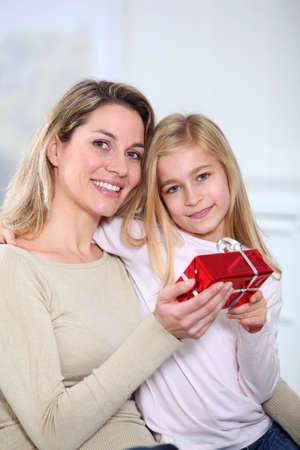 Little girl offering present to her mom