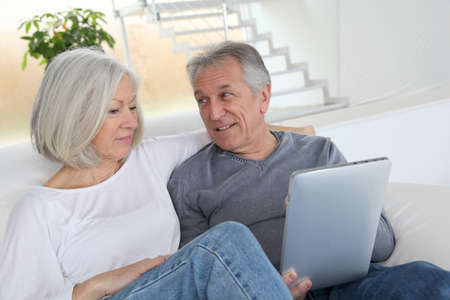 mature couple: Senior couple sitting in sofa with electronic tablet Stock Photo