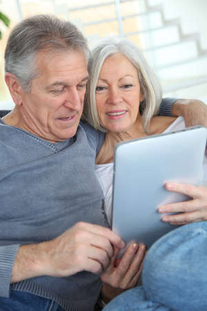 Senior couple sitting in sofa with electronic tablet Stock Photo - 9031632