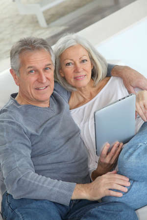 60 years old: Senior couple sitting in sofa with electronic tablet Stock Photo