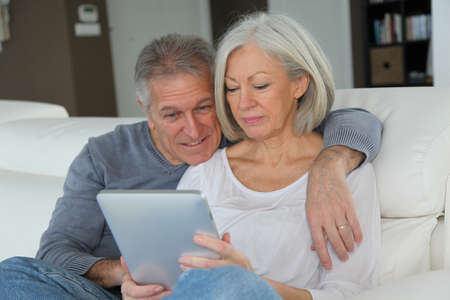 Senior couple sitting in sofa with electronic tablet photo