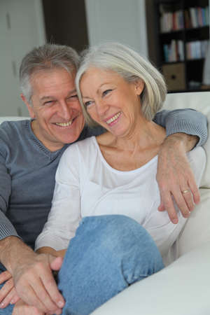 Senior couple sitting in sofa at home photo