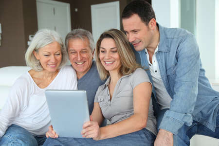Portrait of happy family sitting in sofa with electronic tablet photo