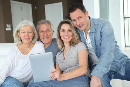 Portrait of happy family sitting in sofa with electronic tablet Stock Photo - 9031633