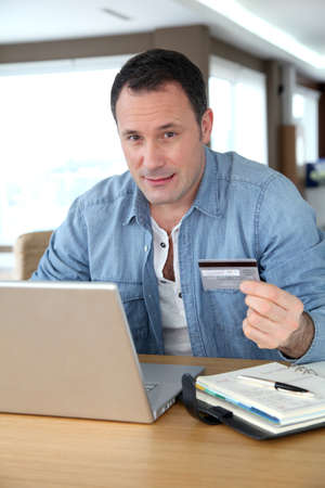 secured payment: Man in front of computer doing online payment