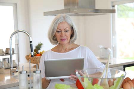 Portrait of senior woman in kitchen photo