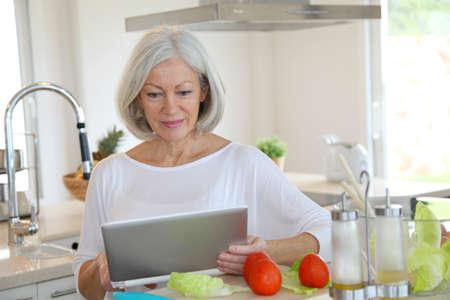 senior ordinateur: Portrait de femme sup�rieur en cuisine