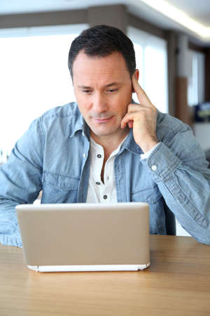 Adult man surfing on internet at home photo