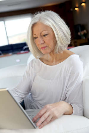 computer age: Senior woman surfing on internet at home