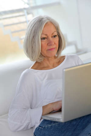 Senior woman surfing on internet at home photo
