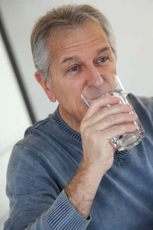 grey water: Senior man drinking glass of water