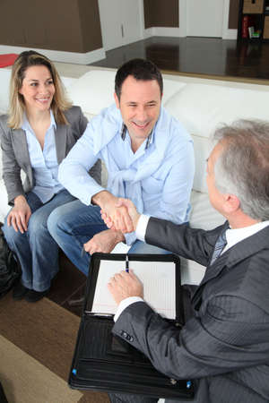 Couple shaking hand to real-estate agent photo