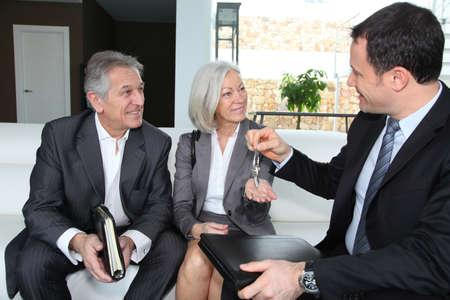 organiser: Real-estate agent giving house keys to senior couple