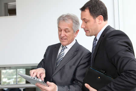 Sales people working on electronic tablet photo
