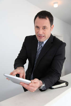 electronic tablet: Businessman standing in hall with electronic tablet