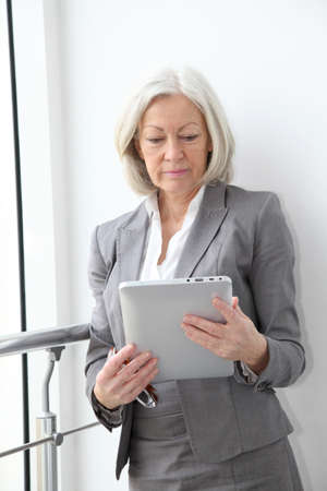 Senior businesswoman using electronic tablet in hall photo