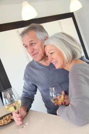 Senior couple drinking wine in home kitchen photo
