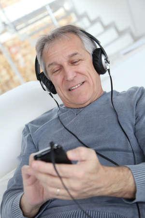 Senior man listening to music with headphones photo