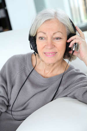 woman listening to music: Senior woman listening to music with headphones Stock Photo