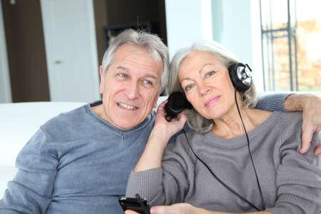 Senior couple listening to music with headphones photo