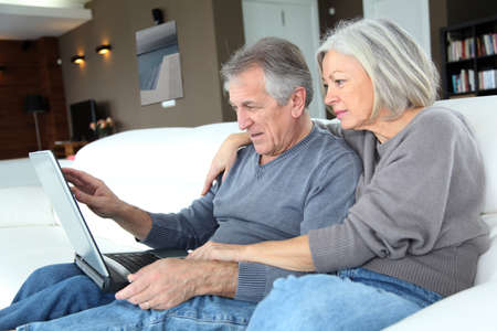 Senior couple surfing on internet at home photo