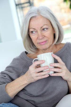 Senior woman drinking hot drink photo