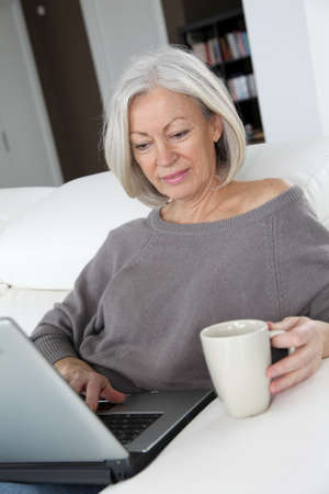 seniors homes: Senior woman relaxing at home in front of laptop computer