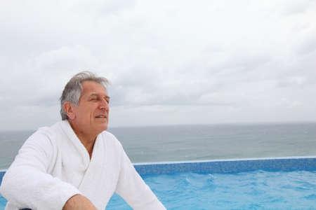 Senior man sitting by pool photo