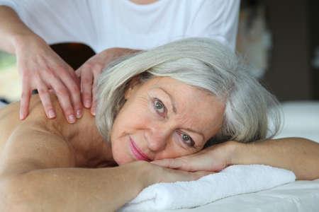massage: Senior Woman eine Massage Lizenzfreie Bilder