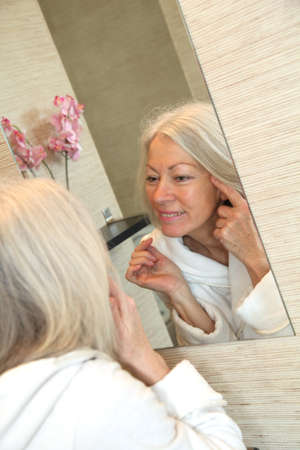 Senior woman applying moisturizer on her face photo