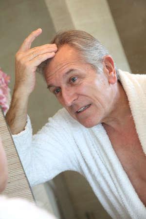 beautycare: Senior man looking at hair in mirror