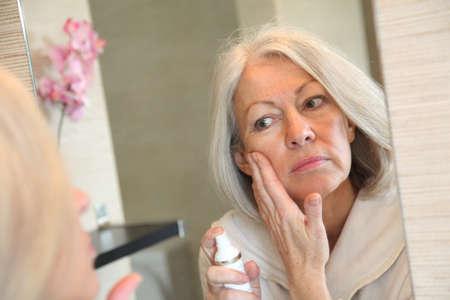 tratamiento capilar: Mujer Senior aplicar crema hidratante en su cara