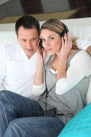 Couple listening to music with headphones photo