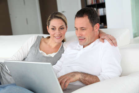 Couple relaxing in sofa with laptop computer photo