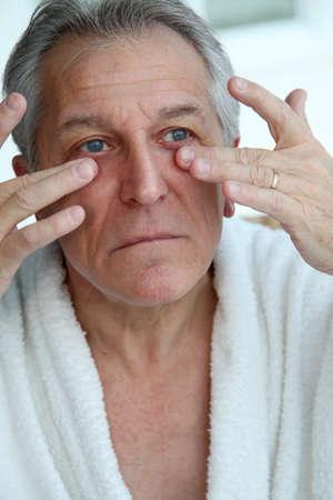 Senior man doing a face massage photo