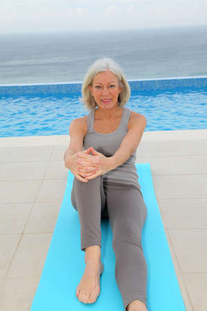 Senior woman doing exercises by a swimming-pool photo