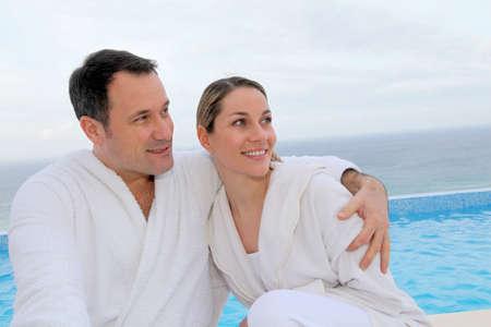 bathrobes: Pareja de Albornoz sentado por piscina
