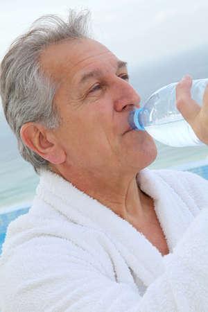 bathrobe: Senior man dinking water from bottle
