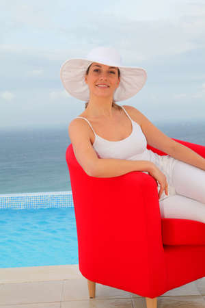 Beautiful woman relaxing in red chair by a swimming-pool Stock Photo - 9031723