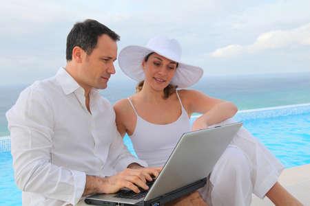 swimmingpool: Couple using laptop computer by swimming-pool