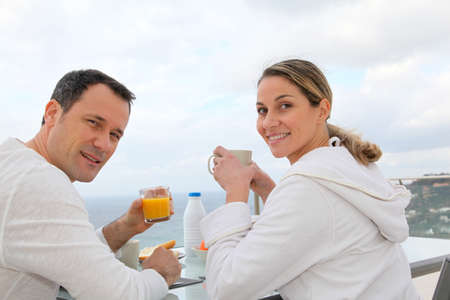Couple having breakfast in their home terrace photo