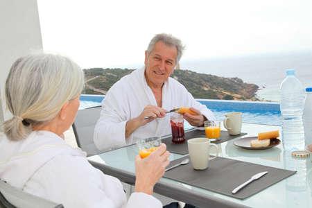 Senior couple having breakfast outside photo