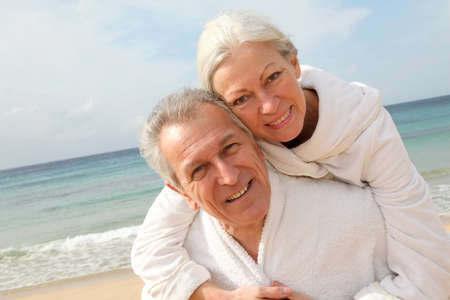 Senior couple in bathrobe at the beach photo