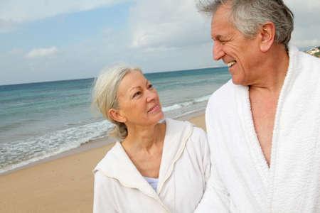 Senior couple in bathrobe at the beach photo