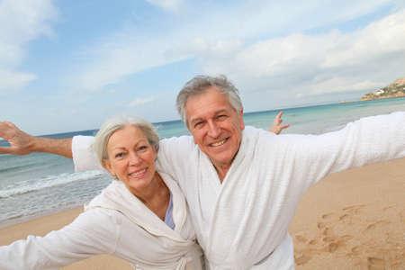 jubilados: Par Senior en Bata de ba�o en la playa Foto de archivo