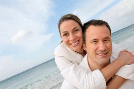Couple relaxing in bathrobe at the beach photo